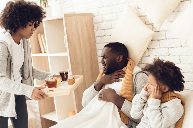 Mother brings father and daughter cough medicine sitting on bed