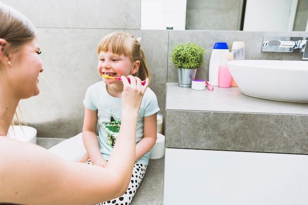 Mother brushing teeth of daughter