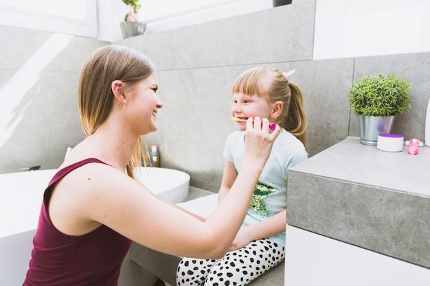 Mother brushing teeth of girl