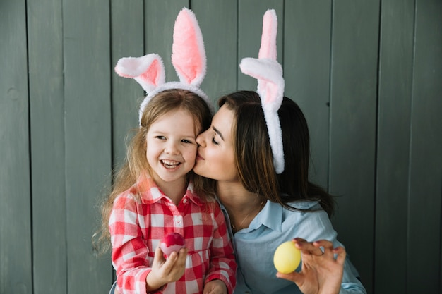 Mother in bunny ears kissing daughter on cheek
