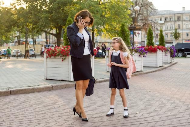 母親の実業家は子供を学校に連れて行きます。