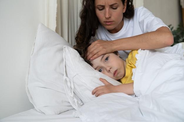 病気の息子の世話をする母親は、手の子供のヘルスケアの概念で子供の体温タッチ額をチェックします