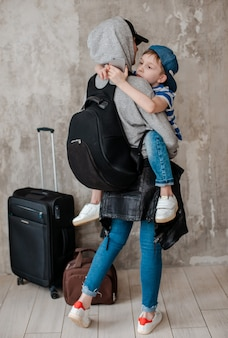 Mother carries a small son on a suitcase in the waiting room of transport.