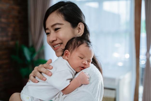 愛らしい小さな娘を運ぶ母