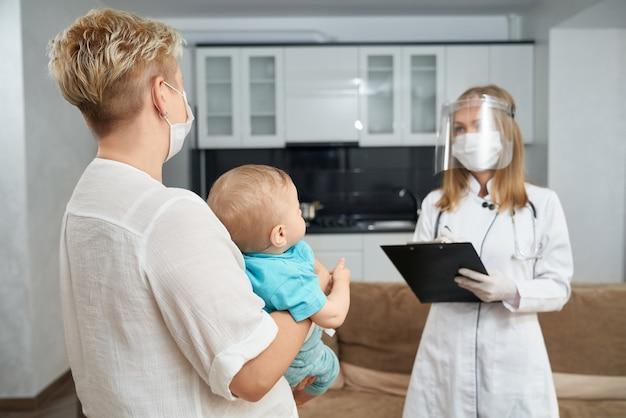 소아과 의사가 검진을하는 동안 아기를 들고 어머니
