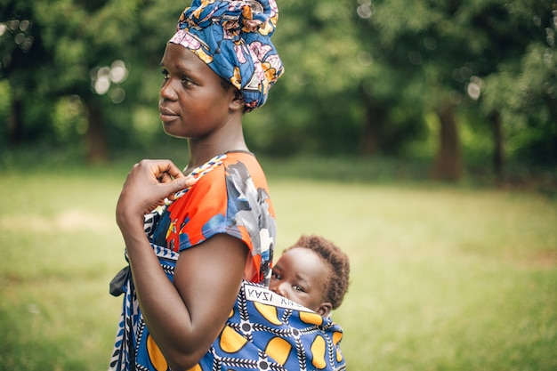 Mother carrying child on back in uganda afric