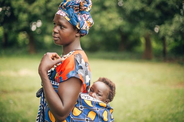 Мать с ребенком на спине в уганде, африка
