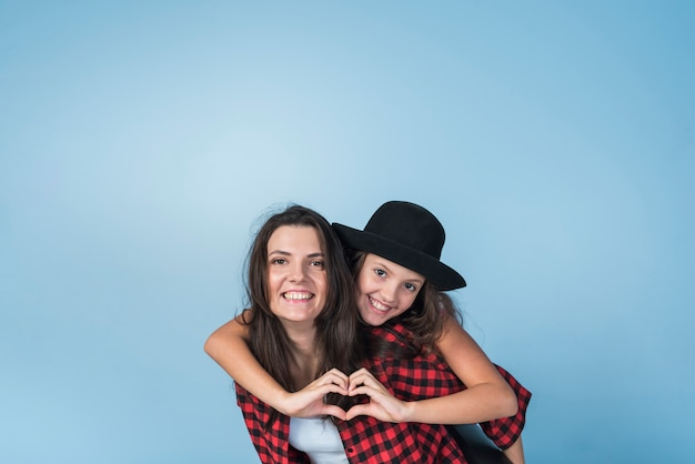 Mother carrying daughter showing heart from hands on back