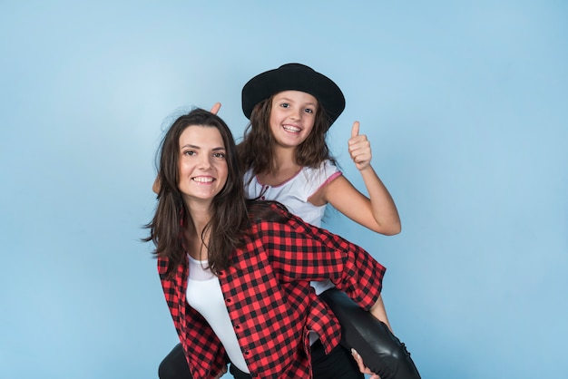 Mother carrying daughter showing thumb up on back