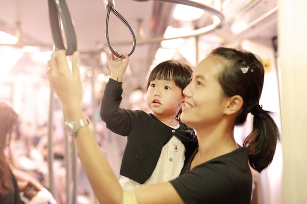 Mother carrying daughter in sky train.
