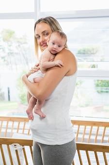 自宅のリビングルームで彼女の赤ちゃんを運ぶ母