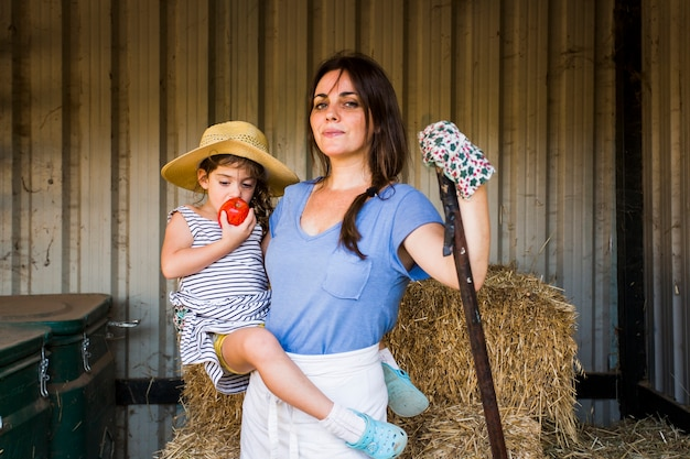 Mother carrying her daughter eating red apple standing in front of hay stack