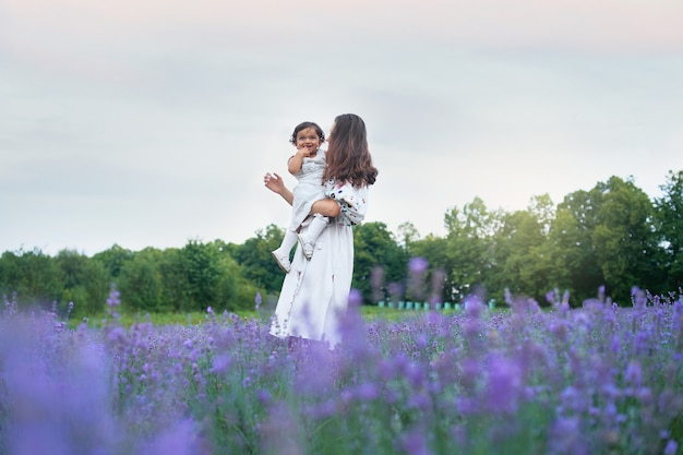 Mother carrying laughing baby and lavender bouquet