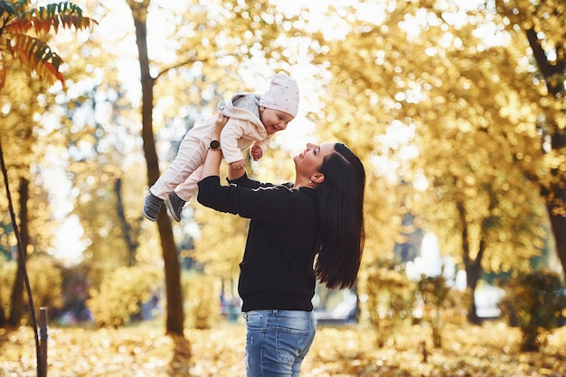 Mother in casual clothes with her child is in the beautiful autumn park.