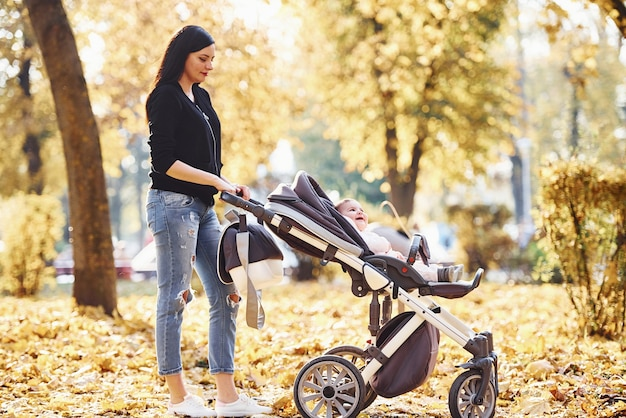 Mother in casual clothes with her child in pram is in the beautiful autumn park.