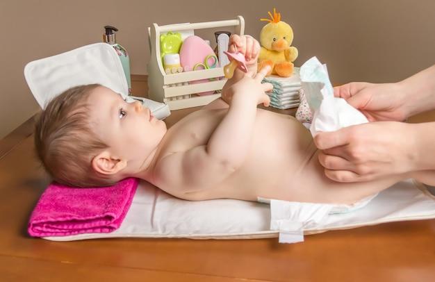 사랑스러운 아기의 기저귀를 갈아주는 엄마