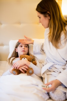 Mother checking fever of her daughter in bedroom