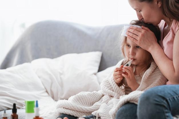 母は娘の体温を体温計でチェックします。テーブルの上の薬。