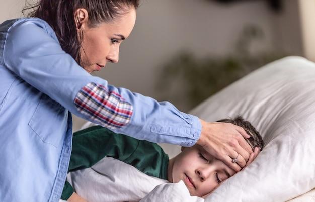 母はベッドで寝ている間に額に手のひらを置いて息子の熱をチェックします。