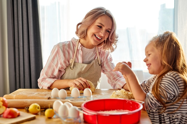 Mother and child daughter are going to cook, bake cookies or pie at home, tasty food for while family, woman and child girl have fun and talk, enjoy the process