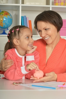 Mother and child daughter putting coins into piggy bank