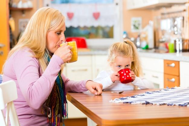 Mother and child drinking milk in kitchen