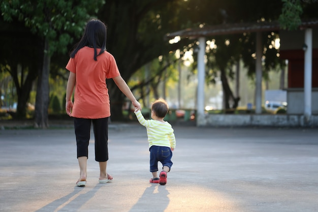 Mother and child holding a hand to walk in the park.