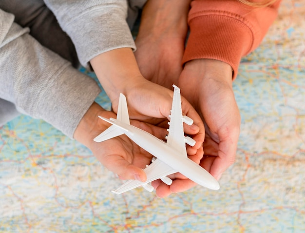 Mother and child at home holding airplane figurine on top of map