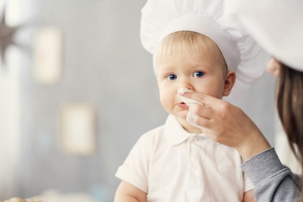 Mother and child on kitchen, white hats of chef, mom wipes baby with help of napkin