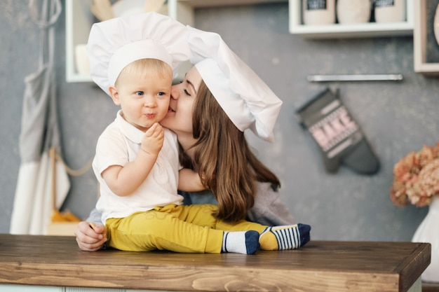 Mother and child on kitchen, white hats of chef, mother kiss her son, relationships of mother and son