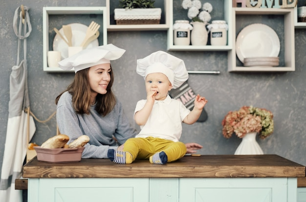 Mother and child on kitchen, white hats of chef