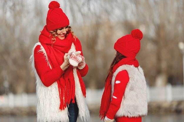 Mother and child in knitted winter hats on family christmas vacation. handmade wool hat and scarf for mom and kid. knitting for kids. knit outerwear. woman and little girl in a park.