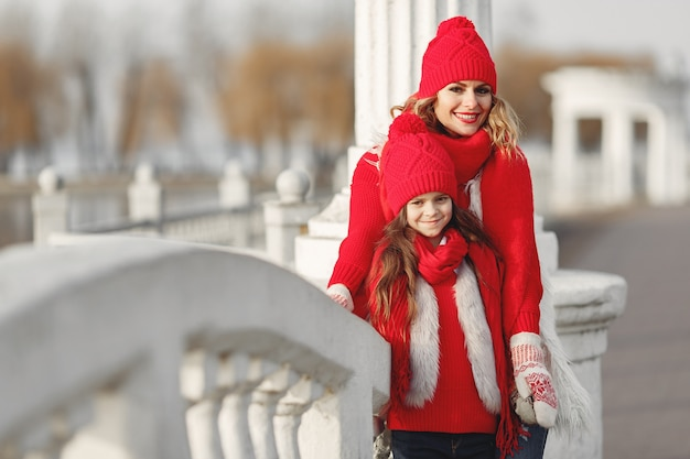 Madre e bambino in cappelli invernali lavorati a maglia in vacanza di natale in famiglia. cappello e sciarpa in lana fatti a mano per mamma e bambino. lavoro a maglia per bambini. capispalla in maglia. donna e bambina in un parco.
