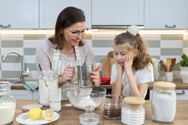 Mother and child preparing bakery together in home kitchen. woman sifts flour, teaches her little daughter how to cook cupcakes. homemade food, family, parent child communication
