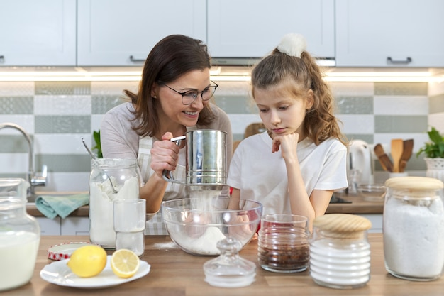 Mother and child preparing bakery together in home kitchen