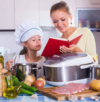 Mother and child preparing meat