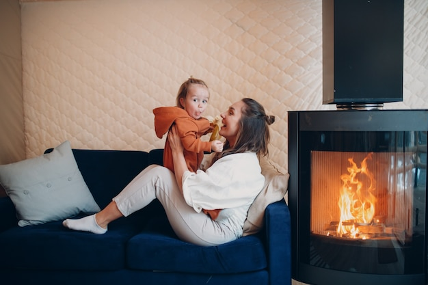 Mother and child sitting and playing on sofa near fireplace mom and baby parent and little kid relaxing at home family having fun together