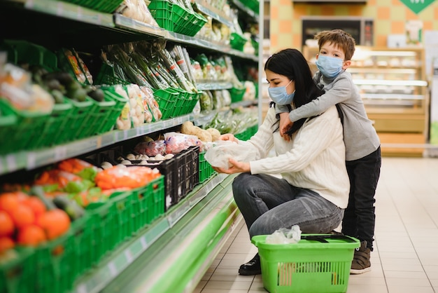 Mother and child in supermarket together, they go shopping freely without a mask after quarantine, choose food together