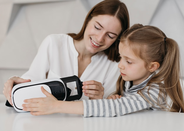 Mother and child using virtual reality headset indoors