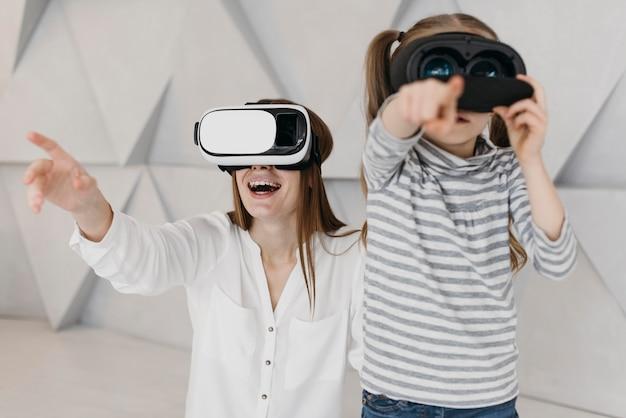 Madre e bambino che utilizzano insieme le cuffie da realtà virtuale
