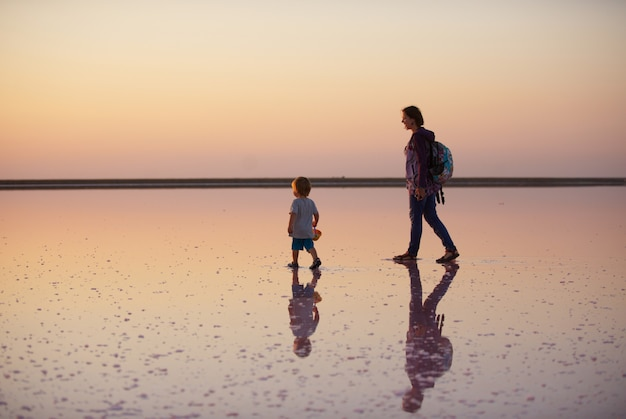 Mother and child walking on a salt and brine of a pink lake,na