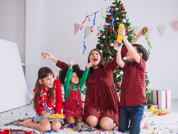 Mother and children are celebrating christmas and having fun and happy in the house with christmas tree