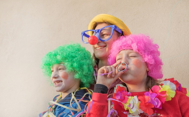 Mother and children in carnival mask smiling togheter outdoor