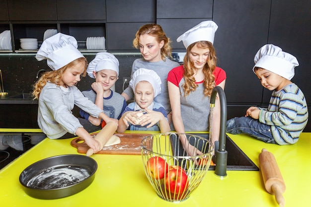 Mother and children cooking in kitchen and having fun