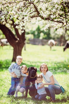 The mother, children and dog sitting on the grass