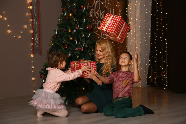 Mother and children exchanging and opening christmas presents