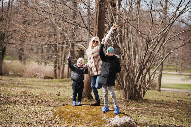 Madre e bambini che giocano su una pietra