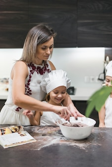 Mother and children preparing dough on messy kitchen counter