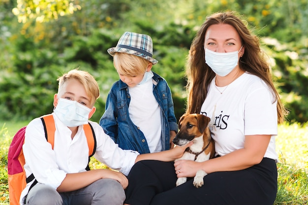Mother and children wearing face protective medical mask. family walking with dog in summer park. coronavirus and real life. kids with puppy outdoors. home animal and pet.