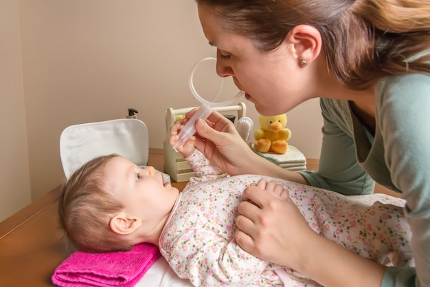Мать, очищающая слизь ребенка с помощью назального аспиратора
